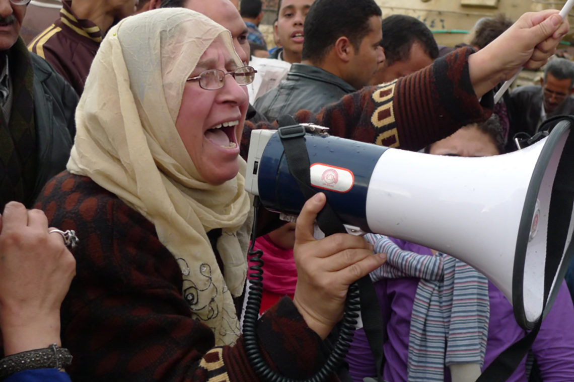 A woman leads chants through a non-functioning megaphone in Tahrir Square near the Egyptian Museum